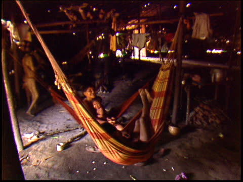 a wide shot of hammocks inside a traditional maloca dwelling - yanomami stock videos and b-roll footage