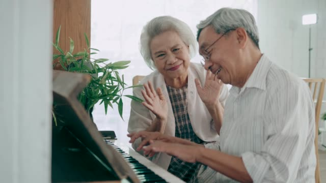 wide shot of  happiness moment of  asian senior couple singing and playing piano at home, 4k resolution - music stock videos & royalty-free footage