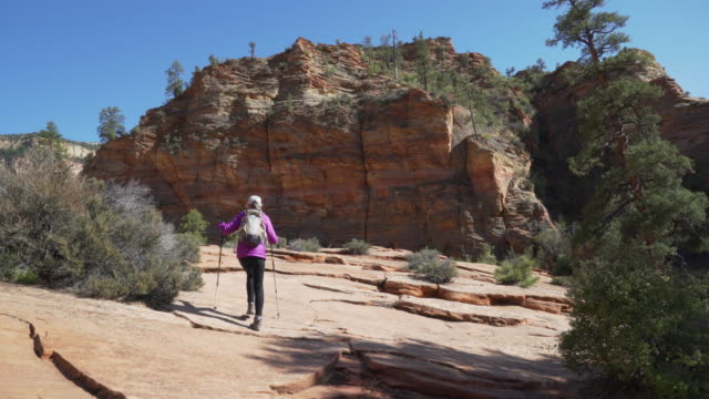 Wide shot of healthy elderly woman hiking towards red sandstone cliff