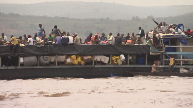 Wide shot of heavy loaded ferry sailing down Congo river