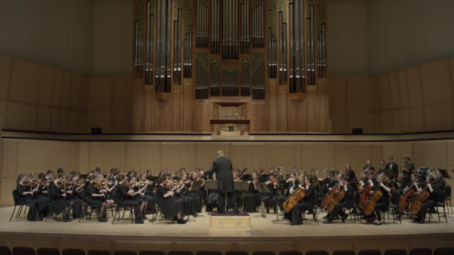 wide shot of high school orchestra performing on stage / salt lake city, utah, united states - orchestra stock videos & royalty-free footage