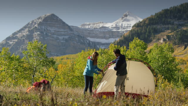 wide shot of hikers assembling camping tent near mountain / american fork canyon, utah, united states - tenda video stock e b–roll