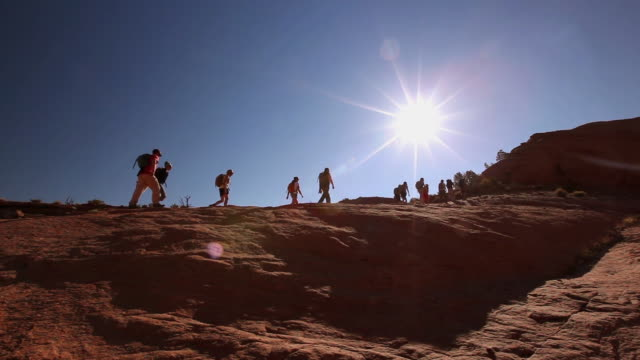 wide shot of hikers hiking up steep red-rock hill in desert with blue skies and sun in utah (pan) - canyon stock videos & royalty-free footage