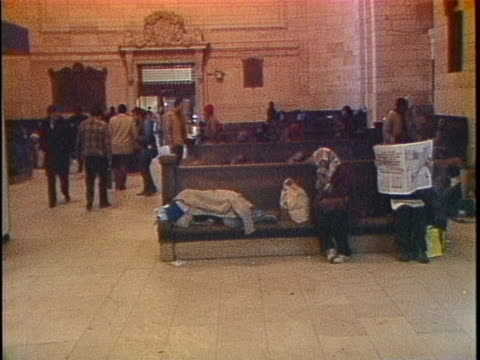 wide shot of homeless people with cardboard boxes sleeping in grand central station, panning to an area of benches for waiting commuters. - 1980 stock videos & royalty-free footage