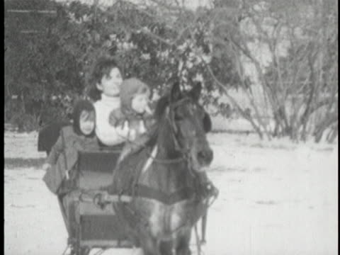 wide shot of horse drawn sleigh on the lawn of the white house slowing riding in the direction of the camera. cut to medium-close tracking shot of... - jackie kennedy stock videos & royalty-free footage