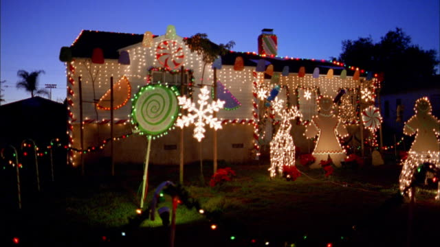 vidéos et rushes de wide shot of house w/christmas display in front yard at night / burbank, california - guirlande lumineuse décoration de fête