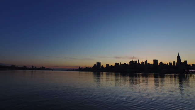 Wide shot of Hudson River at sunrise, with dark New York City skyline at horizon