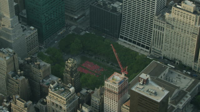 wide shot of hundreds of people doing yoga in the bryant park in new york - bryant park stock videos and b-roll footage