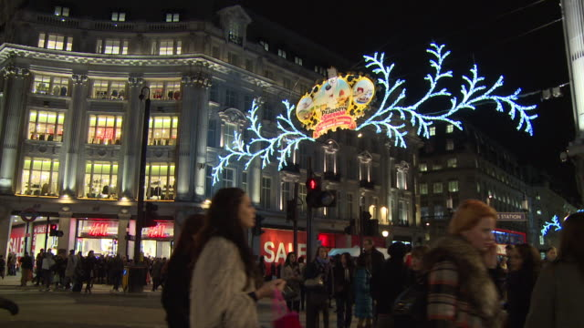 Wide shot of hundreds of shoppers crossing the road at an illuminated Oxford Circus in London, UK.