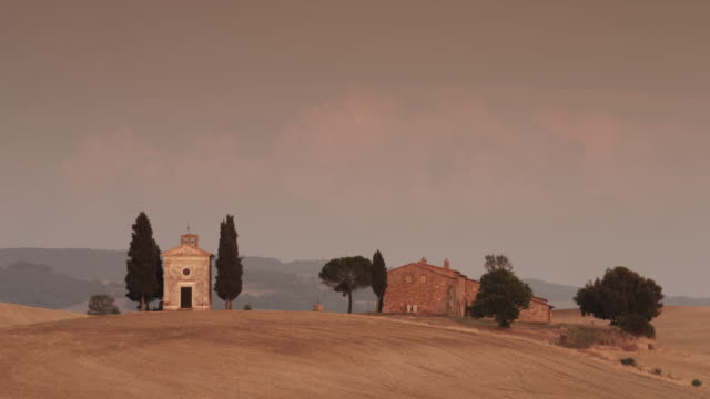 Wide shot of Italian church and farmhouse in countryside / Piensa, Tuscany, Italy