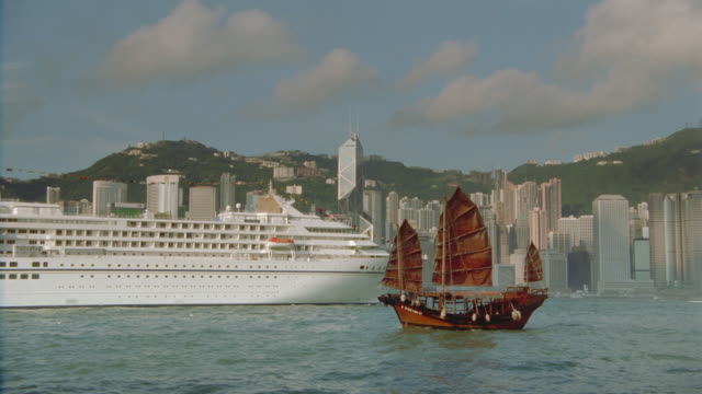 stockvideo's en b-roll-footage met wide shot of junk and cruise ship in harbor with hong kong skyline background - stadscentrum hongkong hongkong