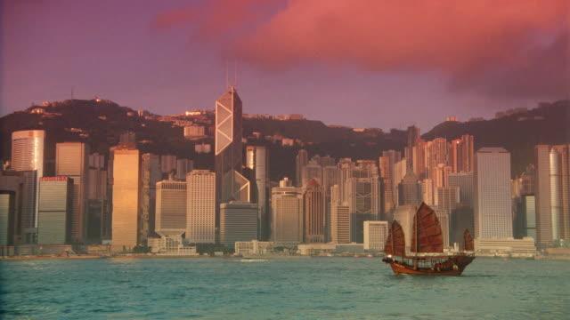 vídeos de stock e filmes b-roll de wide shot of junk in harbor with hong kong skyline in background / filter - 1995