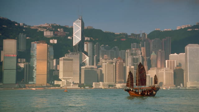 wide shot of junk in harbor with hong kong skyline in background / central district - central district hong kong stock videos & royalty-free footage