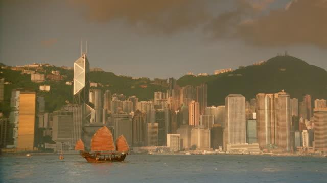 vídeos de stock e filmes b-roll de wide shot of junk in harbor with hong kong skyline in background / central district / filter - 1995