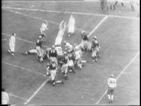 wide shot of kickoff and ball goes out of bounds / medium shot bob brugge runs and is tackled / wide shot les horvath jumps over other players to... - ohio state university stock videos & royalty-free footage
