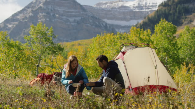 wide shot of man carrying bowl to woman using camping stove / american fork canyon, utah, united states - american fork canyon bildbanksvideor och videomaterial från bakom kulisserna