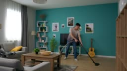 Wide shot of Man cleaning cozy apartment with vacuum cleaner