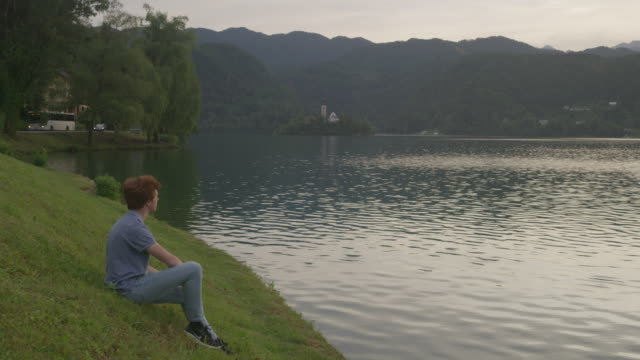 Wide shot of man relaxing at lake / Bled, Slovenia