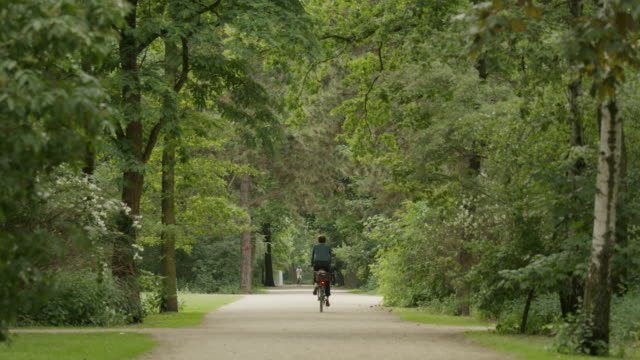 Wide shot of man riding bicycle in park / Berlin, Germany
