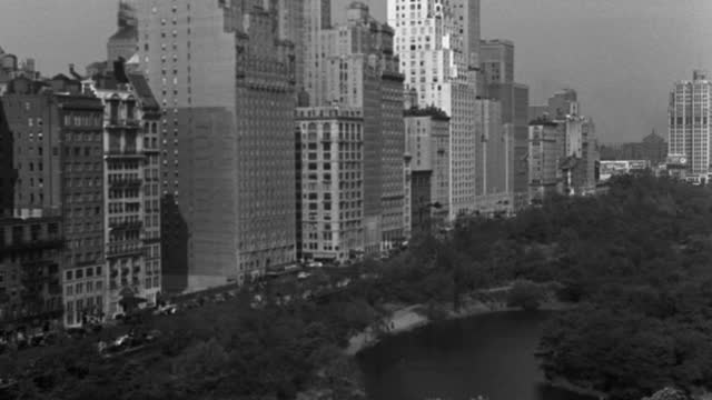 wide shot of manhattan 59th st skyline by central park against sky with lake in foreground, new york city, new york state, usa - 1937 stock videos & royalty-free footage