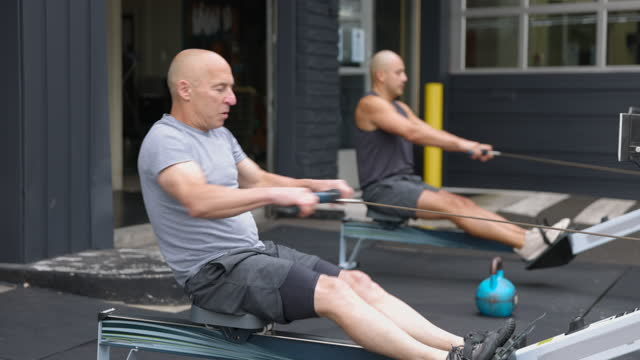 wide shot of mature man working out on rowing machine at outdoor gym - running shorts stock videos & royalty-free footage