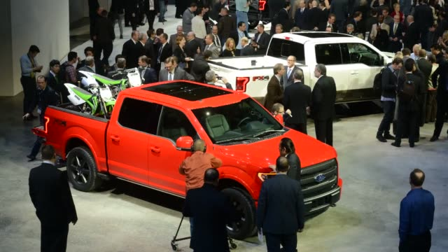 wide shot of members of the media view an white and orange ford motor co f150 pickup truck during the the 2014 north american international auto show... - ford truck stock videos and b-roll footage