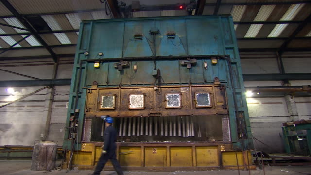 Wide shot of metal parts being lowered into a vat at a galvanising factory in Telford