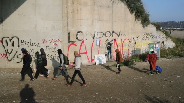 wide shot of migrants leaving the jungle migrant and refugee camp on october 21, 2016 in calais, france. many migrants have left by coach to be... - evacuazione video stock e b–roll