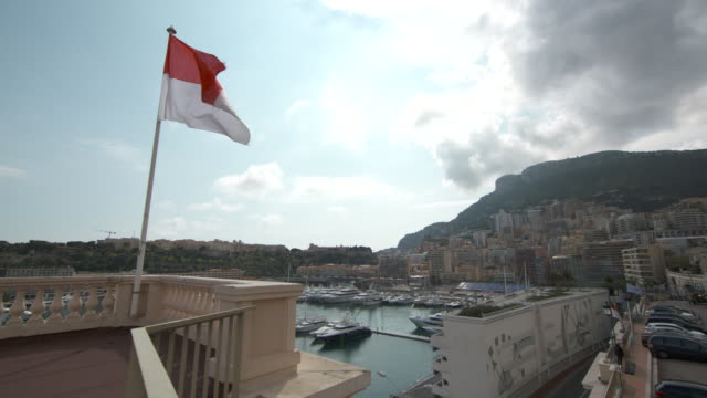 wide shot of monaco harbour with monaco flag flying in the foreground - monaco stock videos & royalty-free footage