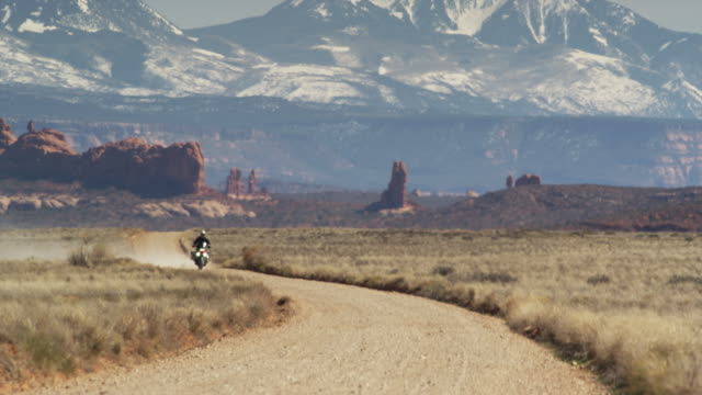 Wide shot of motorcycle approaching on desert road / Arches National Park, Utah, United States