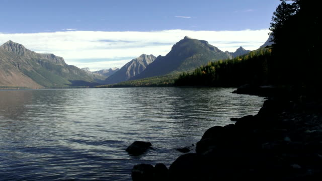 wide shot of mountain lake with rocky shoreline and jagged peaks in background. - seeufer stock-videos und b-roll-filmmaterial