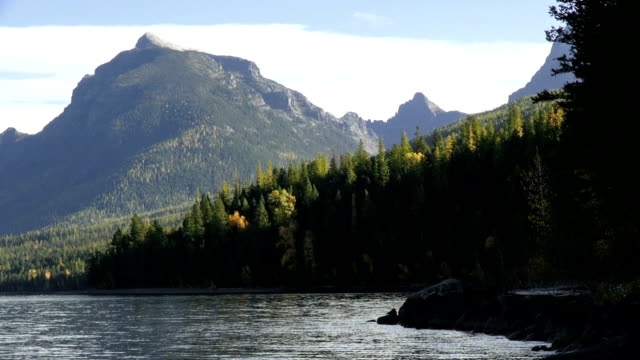Wide shot of mountain lake with rocky shoreline and jagged peaks in background.