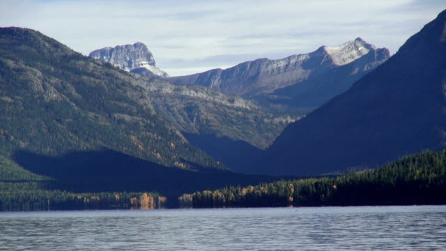 Wide shot of mountain lake with yellow fall trees along shoreline and jagged snow covered peaks in background.