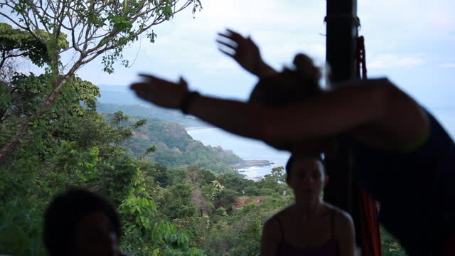 wide shot of mountains and ocean coast line panning out to reveal woman moving into yoga posture who is silhouetted with women sitting and watching at outdoor yoga studio - kelly mason videos stock videos & royalty-free footage