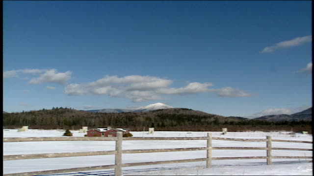 vídeos de stock, filmes e b-roll de wide shot of mountains trees and snow covered field in lake placid, ny - forma da água