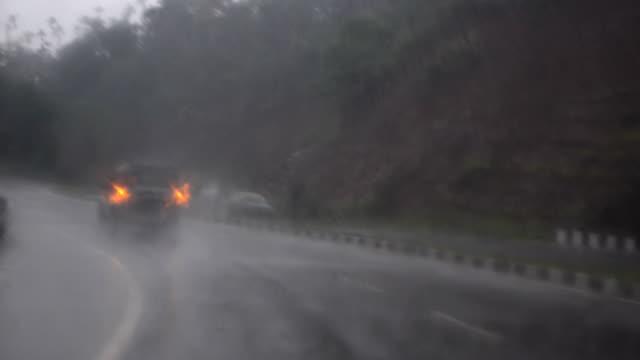 vídeos de stock, filmes e b-roll de wide shot of moving wiper and chasing car crossing hill in rain. - para brisa