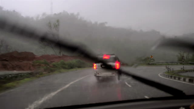 vídeos de stock, filmes e b-roll de wide shot of moving wiper and chasing car in rain. - lanterna traseira