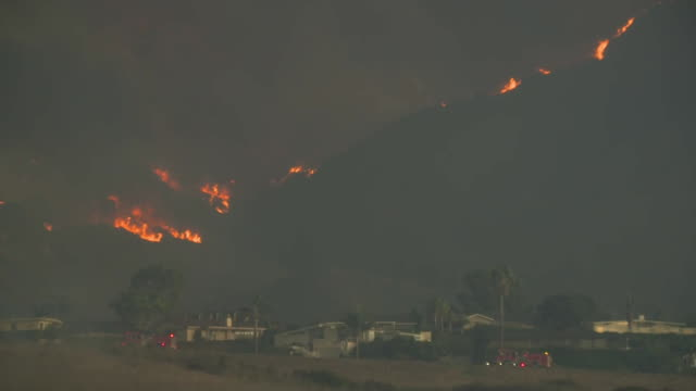 wide shot of multiple wildfires burning on a mountainside behind a community in malibu, california on november 9, 2018. - fire engine stock videos & royalty-free footage