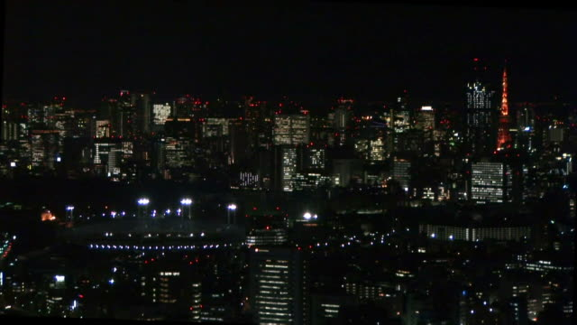 Wide shot of National Stadium and skyscrapers at night / Tokyo