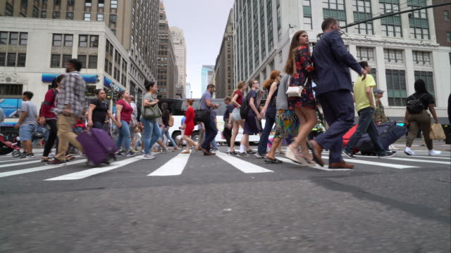 Wide shot of New York City pedestrians using the crosswalk on busy street in Midtown.
