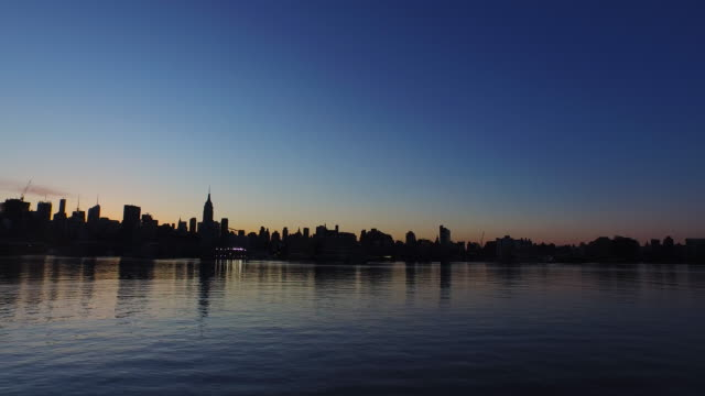 Wide shot of New York City skyline across Hudson River at sunrise