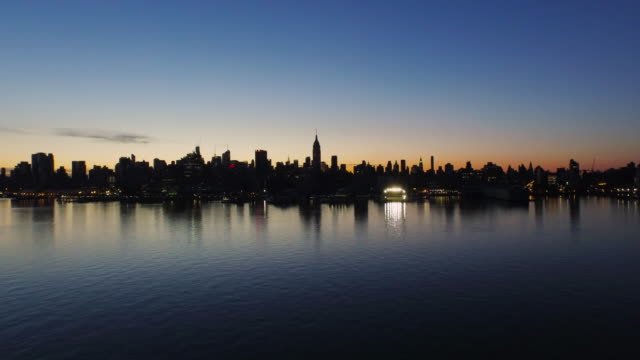 Wide shot of New York City skyline across the Hudson River, silhouetted against orange sunrise