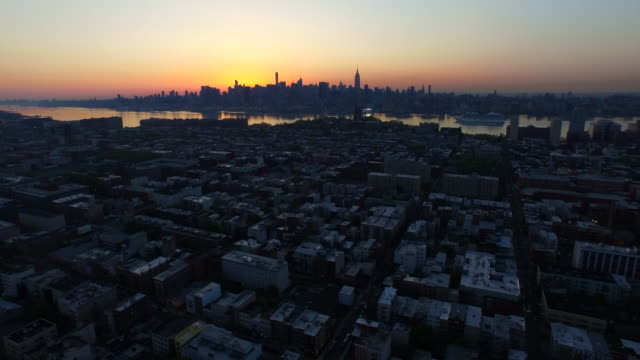 wide shot of new york city skyline against a pink and yellow sunrise in the distance - 50 seconds or greater stock videos & royalty-free footage