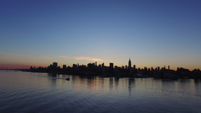 Wide shot of New York City skyline bathed in shadow at sunrise