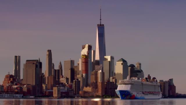 vídeos de stock, filmes e b-roll de wide shot of norwegian cruise ship moving along hudson river in front of new york city skyline - grande