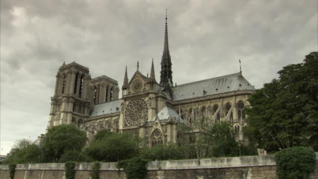 vidéos et rushes de wide shot of notre dame de paris under a moody sky, france. - cathédrale