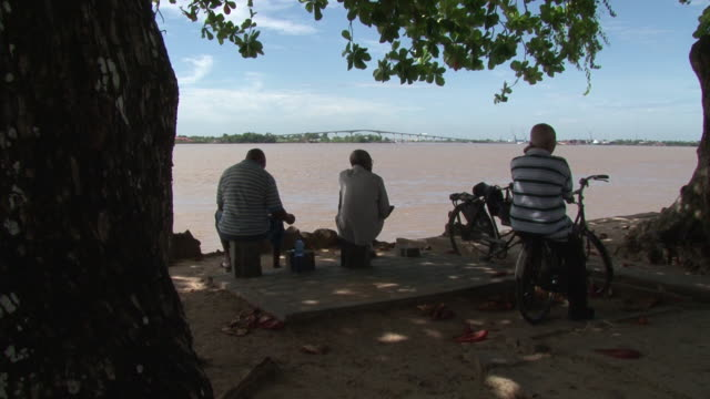 Wide Shot of old men sitting on bank of river in Suriname