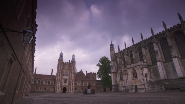 Wide shot of ominous clouds passing slowly over a large courtyard at Eton College, UK.