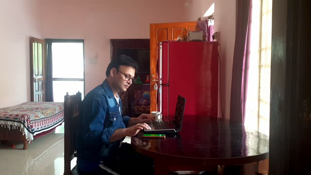 wide shot of one asian / indian male working on laptop & smart phone sitting on dining table in living room of his home holding his tea / coffee mug in morning day light in happy mood during lockdown of covid-19 pandemic - パンツ点の映像素材/bロール