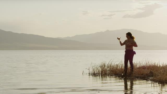 wide shot of park ranger collecting water sample from lake / vineyard, utah, united states - 公園保安官点の映像素材/bロール